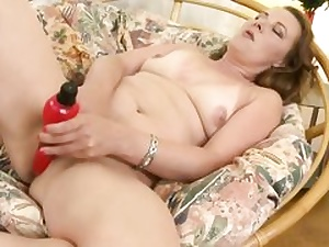 Steamy mummy is feeding her wet honeypot crevasse with a good-sized crimson dildo on couch